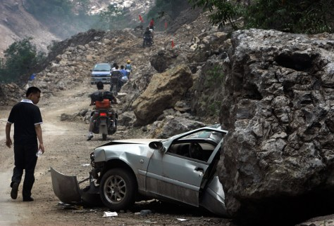 Image: A man looks at a car being half flattened by a huge rock as motorists ride through a damaged road