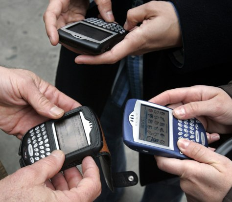 Image: Three people use BlackBerry devices