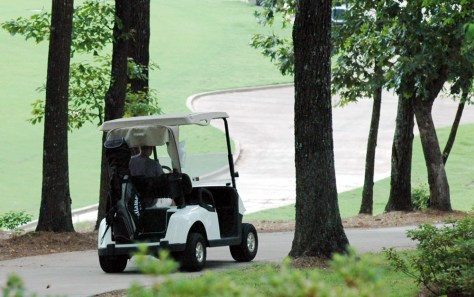 Image: A golfer drives down a hill