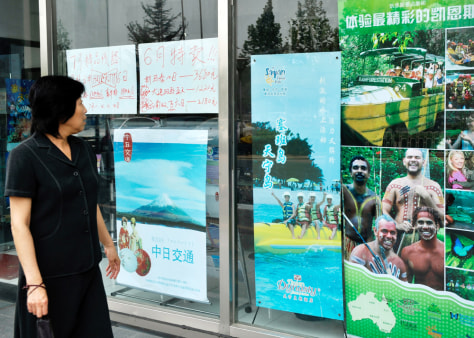 Image: A pedestrian looks at travel promotion posters