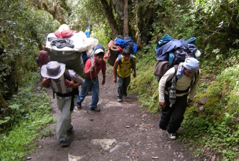 Image: Porters walk along a path during an Inca trail expedition in Cuzco, Peru
