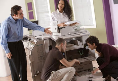 Image: How many office workers does it take to clear a paper jam?