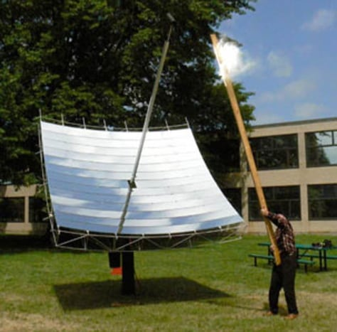 Image: Inventor Doug Wood demonstrates the solar dish's power by using it to set fire to a board held at the focal point.