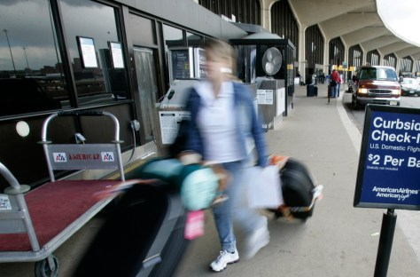 Image: A woman wheels her bags into the terminal