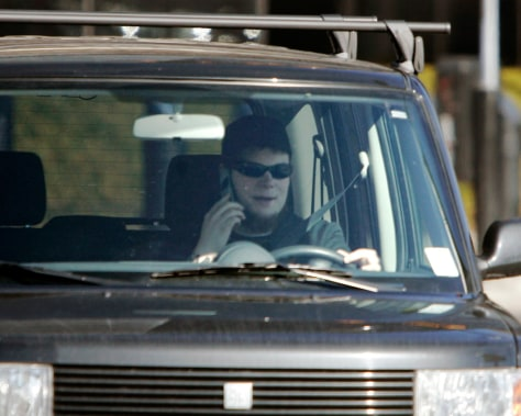 Image: A driver talks on a cell phone while driving