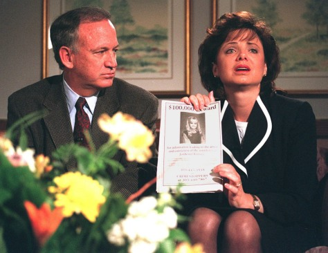 John Ramsey looks on as his wife Patricia holds up