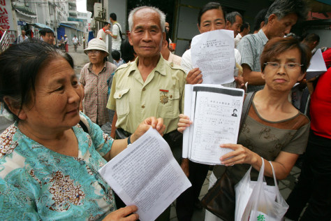 Image: Petitioners hold up documents listing their grievances