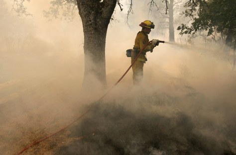 Image: A California Department of Forestry firefighter uses a hose to extinguish hot spots