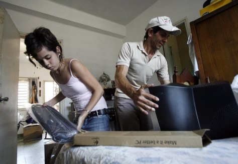 Image: Amanda and her father Pedro unpack a computer they have just purchased in Havana