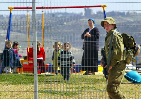 Image: Israeli soldier patrols near playground in West Bank Jewish settlement.