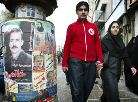 COUPLE WALK HAND IN HAND PAST CAMPAIGN POSTERS