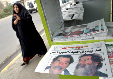 WOMAN PASSES BY IRAQI NEWSPAPER SHOWING SADDAM HUSSEIN IN BAGHDAD
