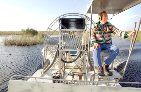 Image: Tribe member on boat in Everglades