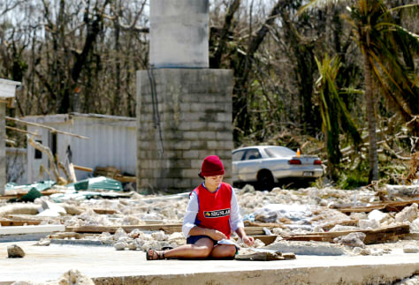 Image: Island resident sits in rubble after cyclone