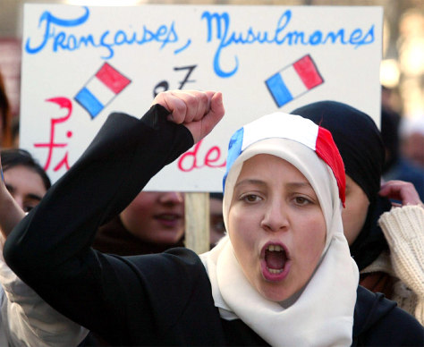 YOUNG MUSLIM WOMEN HOLDS FRENCH FLAG ON HER HEADSCARF DURING PROTEST IN LILLE
