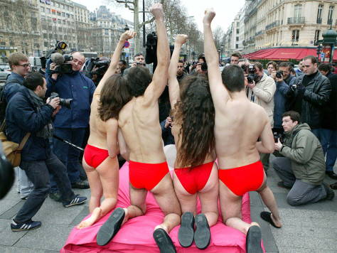 Image: Animal rights activists protest topless in Paris