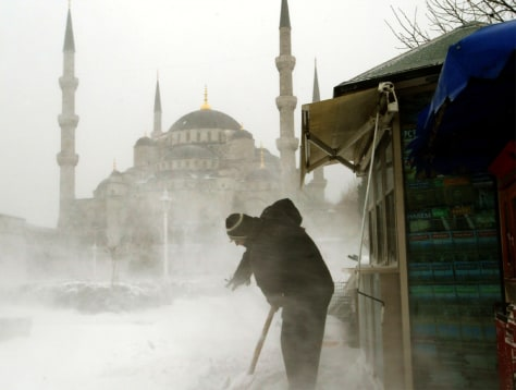 MAN SHOVELS SNOW IN FRONT OF HIS KIOSK NEAR THE BLUE MOSQUE IN ISTANBUL