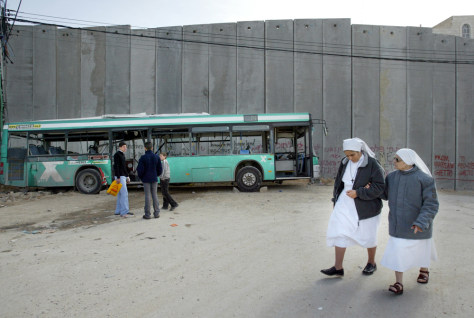 Image: Nuns walk near bombed bus placed in front of West Bank barrier