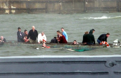 Image: Survivors cling to capsized pontoon.