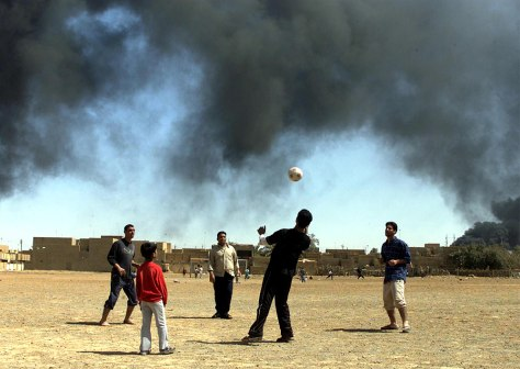 IRAQI BOYS PLAY SOCCER IN FRONT OF SMOKE FROM RAGING OIL FIRES IN BAGHDAD