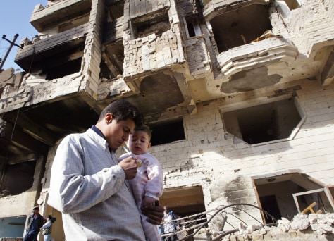 Image: Iraqi man and child; Baghdad hotel destroyed in bombing.