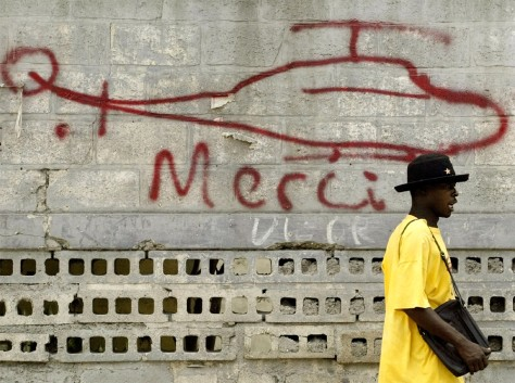 HAITIAN MAN WALKS BY A WALL WITH A GRAFFITI ON A WALL IN PORT AU PRINCE