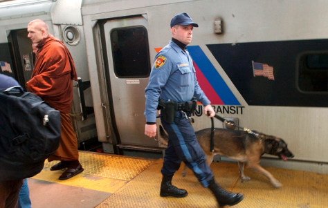 Tranist cop, bomb sniffing dog inspect train.