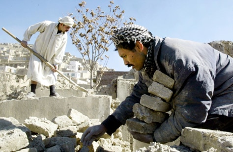 MEN PICK THROUGH RUBBLE