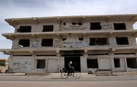 Image: Iraqi man cycles past building previously used by U.S. forces in Fallujah.