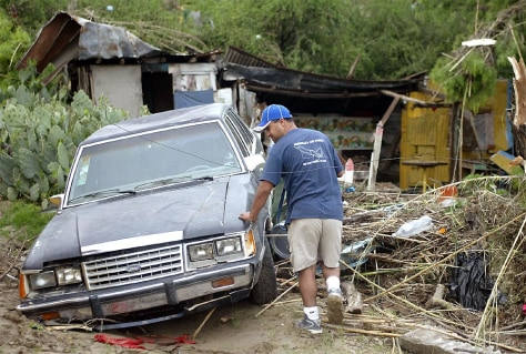 IMAGE: A RESIDENT OF PIEDRAS NEGRAS WALKS BY CAR SWEPT AWAY BY TORRENTS OF WATER