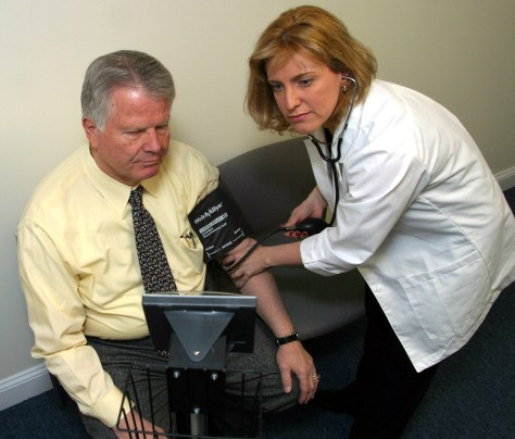 Doctor checks patient's blood pressure