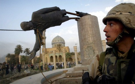 FILE PHOTO OF US SOLDIER WATCHES AS STATUE OF SADDAM HUSSEIN FALLS IN CENTRAL BAGHDAD