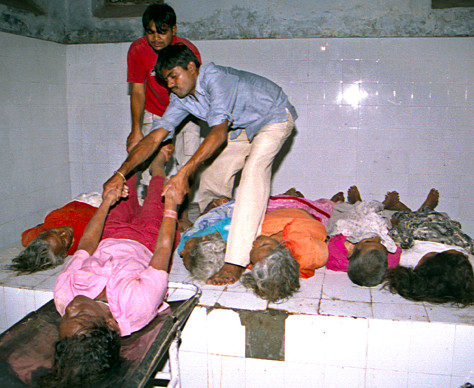 INDIAN PARAMEDICS LOAD DEAD BODIES INTO A HOSPITAL MORGUE AFTER A STAMPEDE IN LUCKNOW