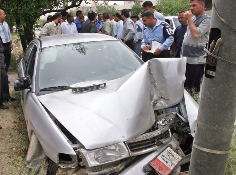 IRAQI POLICE STAND NEXT TO WRECKAGE OF IRANIAN DIPLOMATIC VEHICLE FOLLOWING ATTACK IN BAGHDAD