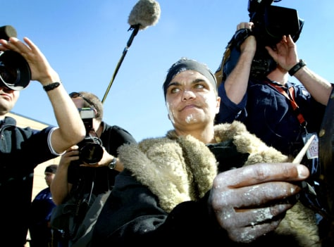 AN ABORIGINAL WOMAN, KNOWN AS MOOPOR, POINTS A KANGAROO BONE AT AUSTRALIAN PRIME MINISTER HOWARD IN COLAC