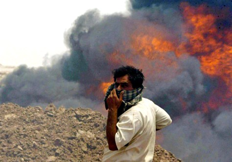 IRAQI MAN COVERS HIS FACE AS HE WATCHES A BURNING OIL PIPELINE NEAR BASRA