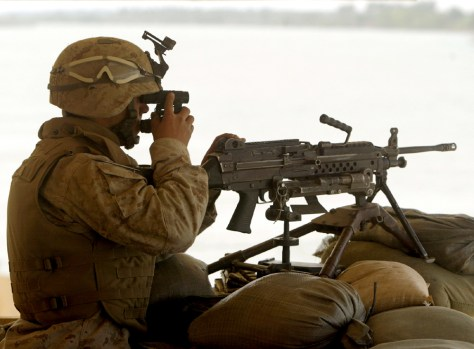 A U.S. MARINE IS SILHOUETTED BY EUPHRATES RIVER WHILE KEEPING SECURITY IN SAQLAWIYA IRAQ