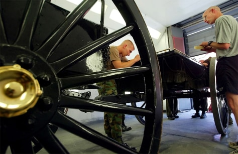 IMAGE: Spc. Jason Dye and Sgt. Robert Dodge of the 3rd U.S. Infantry Regiment at Fort Myer, Va., prepare the caisson used in the funeral services for former President Ronald Reagan.