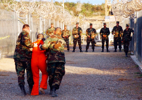 FILE PHOTO OF US MILITARY ESCORTING DETAINEE TO CELL AT XRAY NAVAL BASE