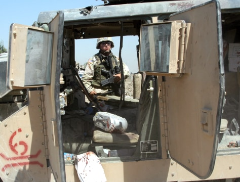 U.S. ARMY SOLDIER LOOKS AT WRECKAGE OF MARINES HUMVEE IN BAGHDAD
