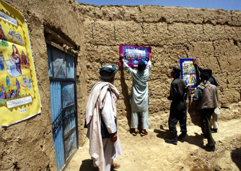 Image: Afghan election officials put up posters.