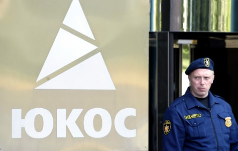 A SECURITY GUARD STANDS OUTSIDE YUKOS HEADQUARTERS IN MOSCOW