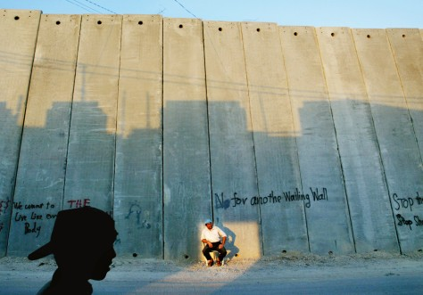 Image: Palestinian sits next to Israeli separation barrier.