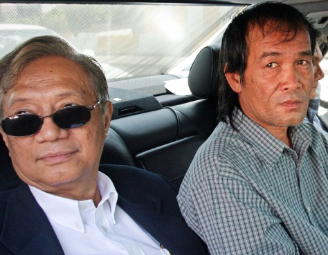 Image: Freed Filipino hostage, right, leaves embassy in Baghdad.