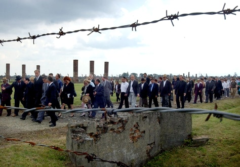 IMAGE: Gypsies march from the former inmate barracks to the ruins of a gas chamber at Auschwitz-Birkenau.