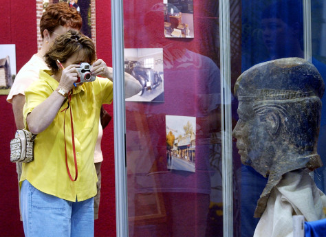 Image: Woman photographs statue of Saddam Hussein's head.