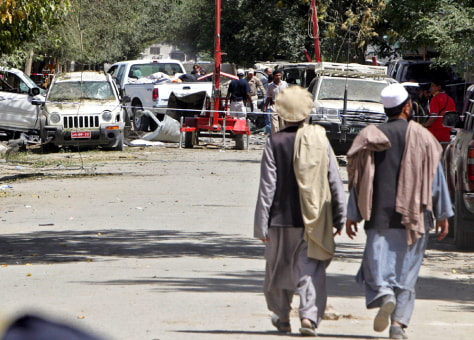 Image: Afghan men walk near site of Kabul bomb blast.