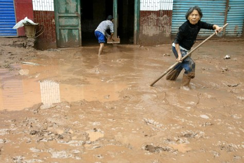 Local residents clear mud outside their home after floods receded in Kaixian