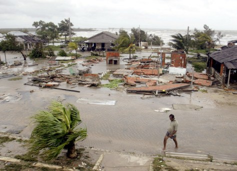 Image: Cuban walks on flooded street near damaged houses.