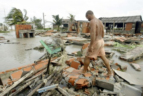 Man walking over debris of destroyed house after Hurricane Ivan brushes Cuba